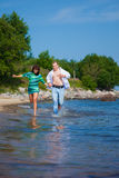 Enamored couple running along the coast of sea Royalty Free Stock Images