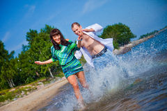 Enamored couple running along the coast of sea Stock Images
