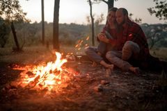 Enamored couple sits on picnic on background of bonfire flame. Enamored couple sits on picnic in forest on background of bonfire flame and sparks stock image