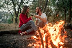 Enamored couple sits and smiles on picnic in forest on bonfire f. Lame background. They hold glasses of wine in hands royalty free stock images