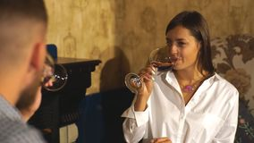 Enamored couple sitting in a chair and drinking wine in a cafe or restaurant. Two people, man and woman in cafe communicate, laughing and enjoying the time stock footage