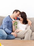 Enamored couple sitting together on the sofa Stock Photography