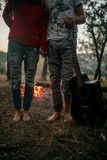 Enamored couple stands with guitar on picnic in forest. Enamored couple stands barefoot with guitar on picnic in forest against background of bonfire flame royalty free stock photos