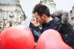 Enamored couple in winter clothes is kissing outdoors with a heart shaped red balloons on foreground. Enamored men and women having fun together at winter day stock photography