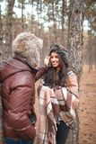 The guy carefully adjusts the fur hat on the girl`s head, the girl smiles coyly. Outdoors. Stock Photo