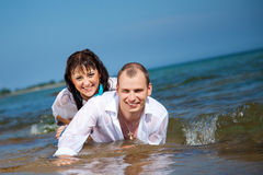 Enamored man and girl lying in waves of sea Stock Photos