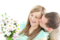 Enamored man giving a bouquet to his girlfriend. Against a white background royalty free stock photo