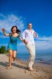 Enamored Paare, die entlang die Küste von Meer laufen Lizenzfreie Stockfotos