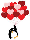 Enamored penguin flies on heart balloons Stock Image