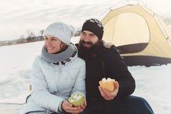 Enamored senta-se junto na neve e olha-se na distância imagens de stock royalty free