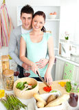 Enamored young couple cutting vegetables at home Royalty Free Stock Images