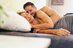 Enamored young couple lying on bed. Together in the bedroom. Happy men and women waking up in morning royalty free stock photo