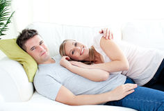 Enamored young couple lyingo together on the sofa. In the living room royalty free stock photo