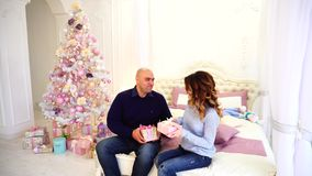 Enamored young parents in festive mood exchange Christmas presents and sit in bedroom with Christmas tree. Man and woman give presents to each other with joy stock video footage