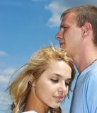 Enamoured couple. The young beautiful woman and the young beautiful man embrace against the dark blue sky clouds Royalty Free Stock Photography