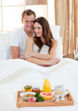 Enamoured couple having breakfast lying in bed Stock Image