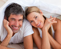Enamoured couple having fun lying on bed Stock Image
