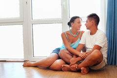 Enamoured couple sitting on floor near window Stock Images
