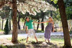 Enamoured guy and the girl walk in wood. Young men, in the summer, in pine wood. A sunny day Stock Images