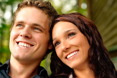Enamoured pair closeup. Young man and woman look afar and laugh stock images
