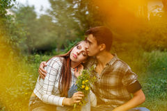 Enamoured teens together. Girlfriend and boyfriend together. The boy hugs a girl. A girl holding a bouquet of wildflowers. Creative shooting. First love. He Stock Photography