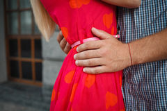 Enamoured young people holding hands and hugging. Detail of holding hands of a loving couple Royalty Free Stock Photos
