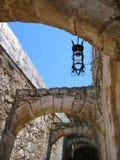 Enangoste la calle con los arcos de piedra y la linterna vieja Fotos de archivo libres de regalías