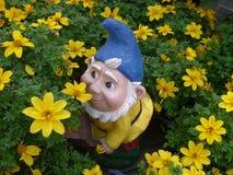Enano del jardín en una cama de flor Fotos de archivo