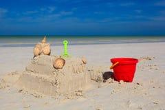 Enarene el castillo con las cáscaras empleadas la playa tropical Fotografía de archivo