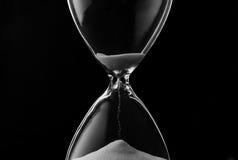 Enarene el goteo a través de los bulbos de un reloj de arena Fotos de archivo