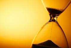 Enarene el paso a través de los bulbos de un reloj de arena Foto de archivo libre de regalías