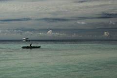 Enarene la playa, el mar y el cielo azul mezclando en el horizonte con un barco de pesca Fotografía de archivo