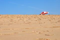 Enarene la playa y el parasol sobre el cielo azul Foto de archivo