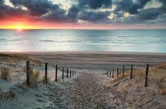 Enarene la trayectoria a la playa de Mar del Norte en la puesta del sol Fotografía de archivo