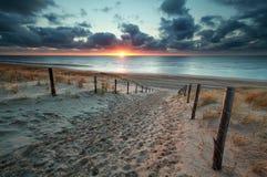 Enarene la trayectoria a la playa de Mar del Norte en la puesta del sol Fotos de archivo libres de regalías