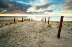 Enarene la trayectoria a la playa de Mar del Norte en la puesta del sol Imagenes de archivo