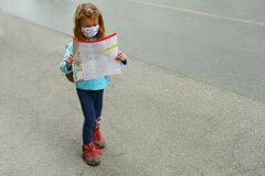 Female child alone walk on a street wearing protective face mask while reads the city map