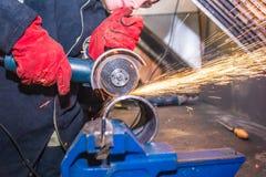 Enbehandskad mekaniker gör ren en svetsad söm på ett avsnitt av ett stålrör med hjälpen av en malande maskin arkivbilder