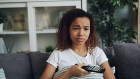 Encabritado de la muchacha afroamericana joven emocional que ve la TV el sentarse en el sofá cómodo y el llorar sobre película tr metrajes
