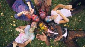 Encabritado del grupo multi-étnico de la gente relajada que miente en hierba así como caras y ropa coloreadas, mirando la cámara metrajes