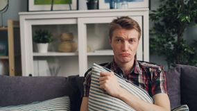 Encabritado del hombre joven emocional que llora sobre película triste en la TV que se sienta en el sofá cómodo y que se consider almacen de video