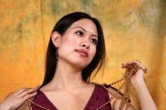 Encadenamiento asiático de la muchacha y del oro Fotos de archivo