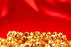 Encadenamiento del oro en un fondo rojo Imagen de archivo
