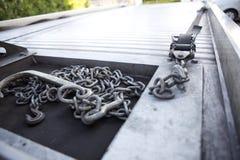 Encadenamientos que se reclinan sobre la cama de un carro de remolque Foto de archivo
