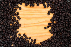 Encadrez la vue écrite par le grain de café rôti sur le fond en bois de table Image stock