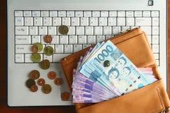 Encaissez l'argent dans un portefeuille en cuir et les pièces de monnaie sur un ordinateur portable Image libre de droits