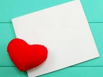 Encaissez la carte blanche et le jour de valentines rouge de coeur sur le fond vert Photographie stock libre de droits
