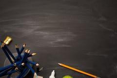 Encaissez le récipient avec les crayons et les fournitures de bureau colorés sur le panneau de craie noir photo libre de droits