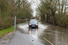encaissez les passages holidaycar par la route inondée avec la mesure d'avertissement et de mesure Image stock