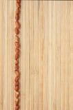 Encaixota uma faixa do amendoim que encontra-se na esteira de bambu Fotos de Stock